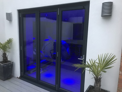 Anthracite Grey Three Segment Bifolding doors into render with blue backlight