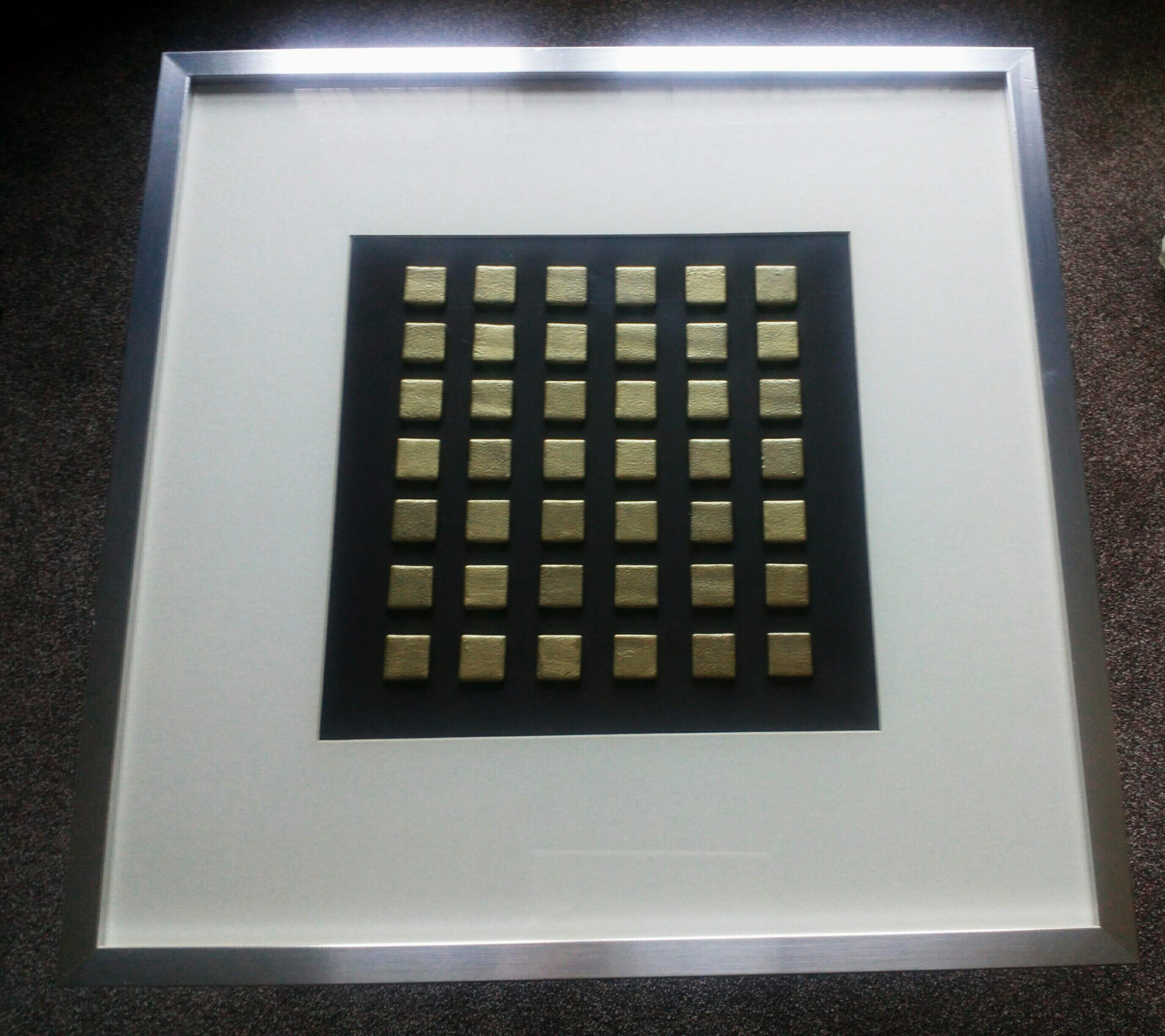 Gold glass tiles mounted on board. Brushed aluminium frame.