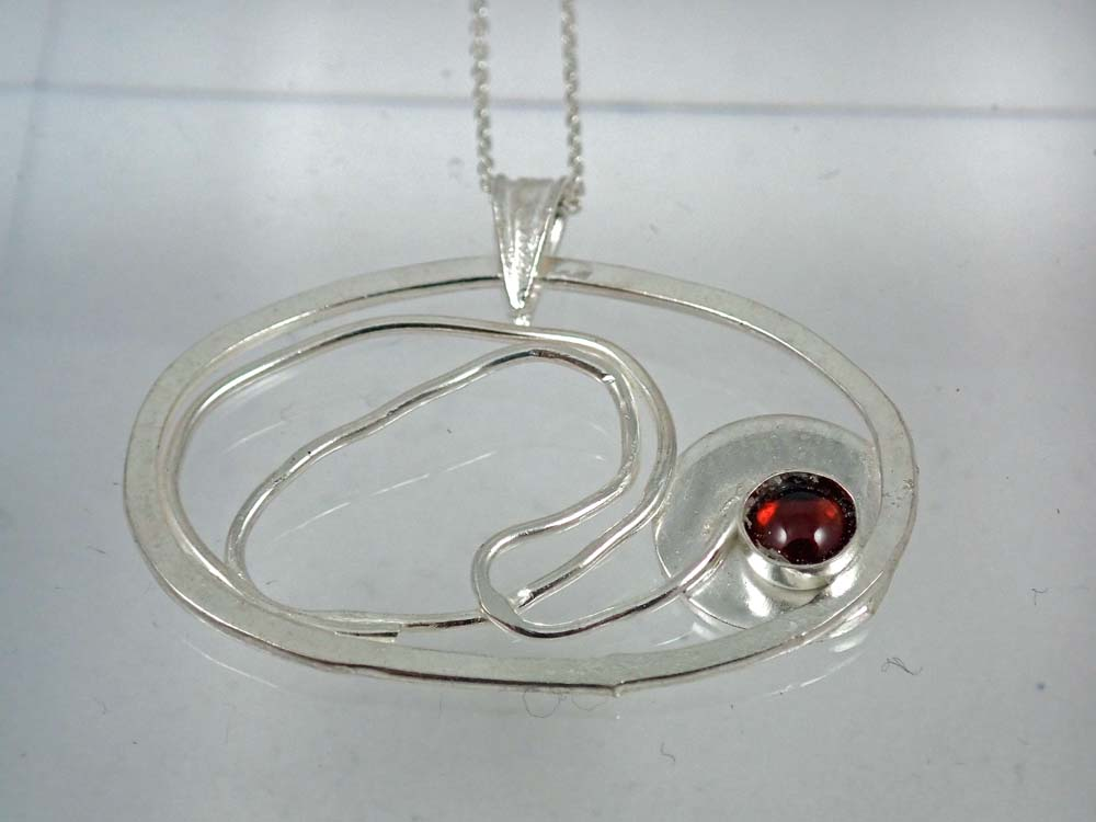 Filigree small pendant with circle and garnet