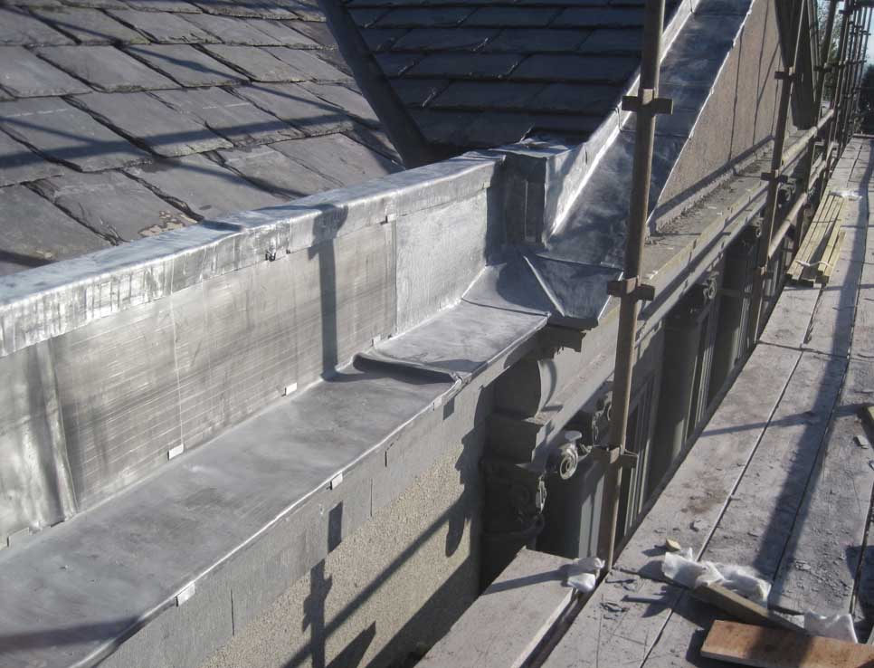 Newly slated roof with parapet stones covered with lead sheath to stop persistent dampness