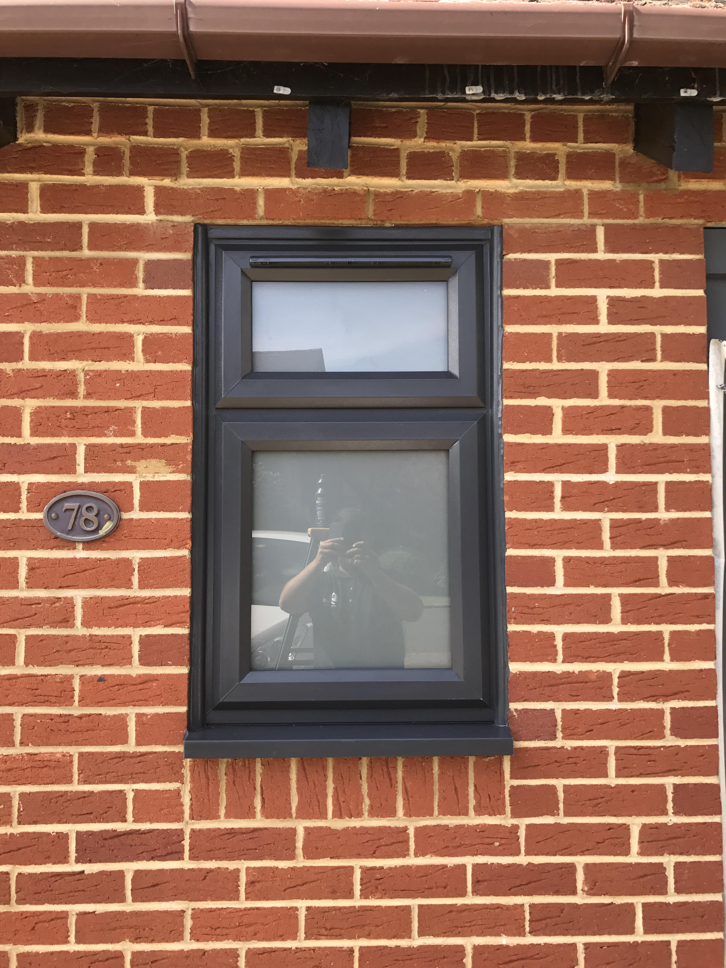 Casement window in PVCu with dummy sash and trickle vent, top opener