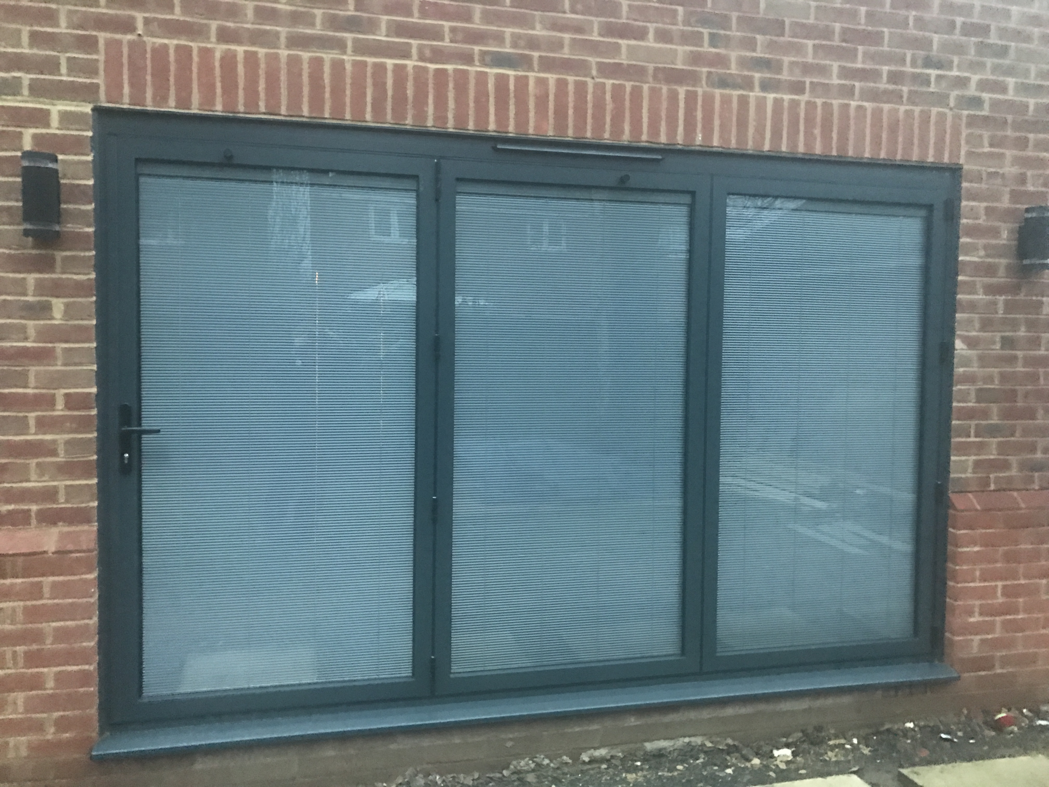 Aluminium Bifolding Doors with integral blinds in glass units.  Opening created, soldier bricks abov