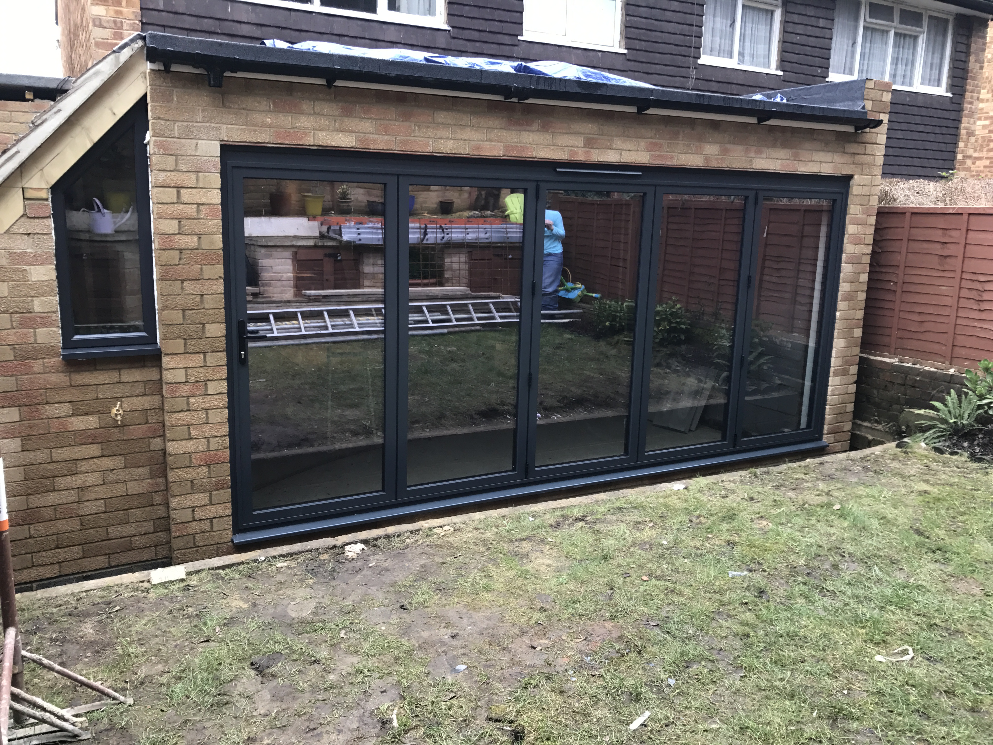 Aluminium Shaped fixed window and bifolding doors fitted into extension