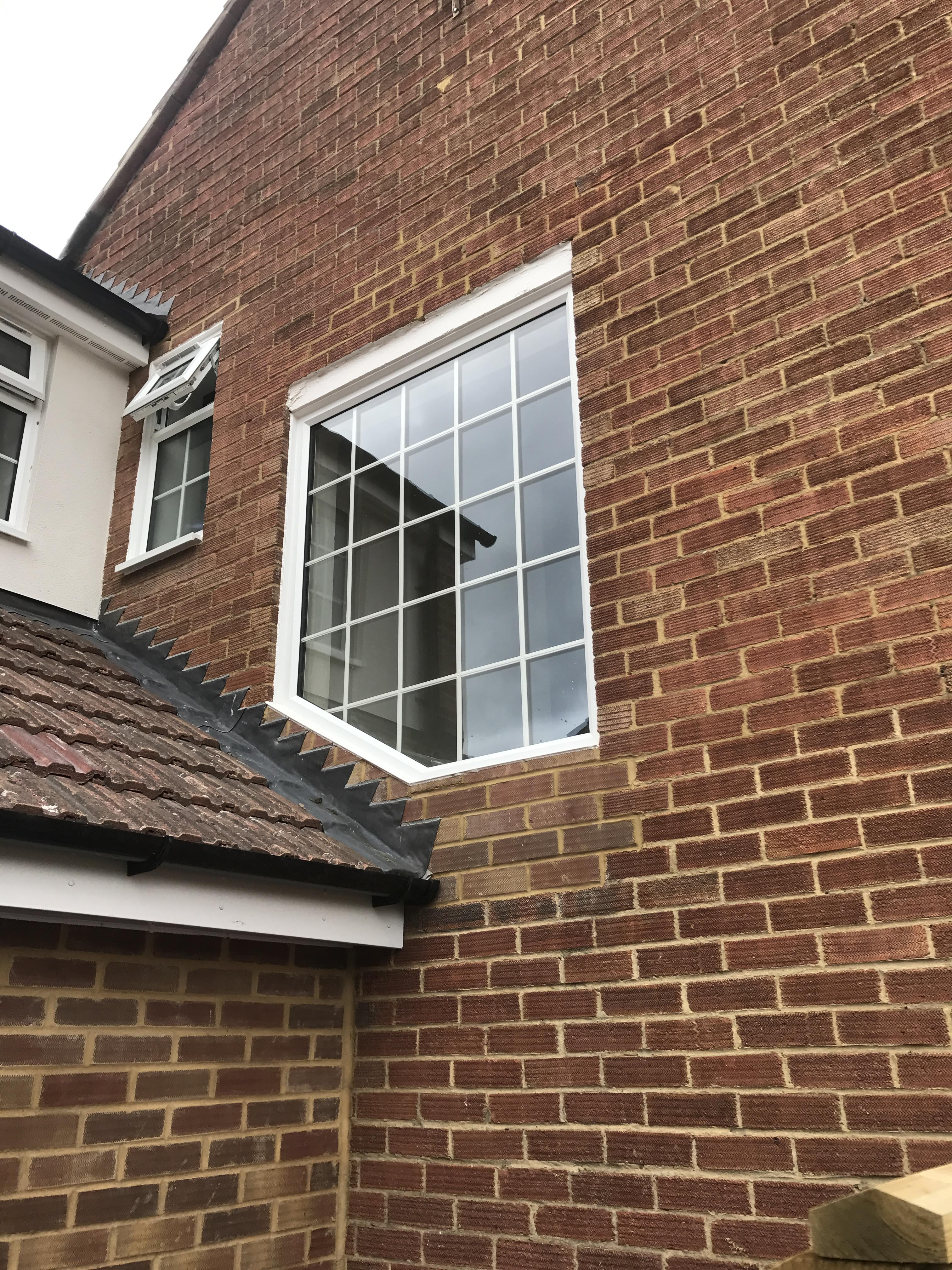 PVCu shaped fixed window with white Georgian bar in sealed unit