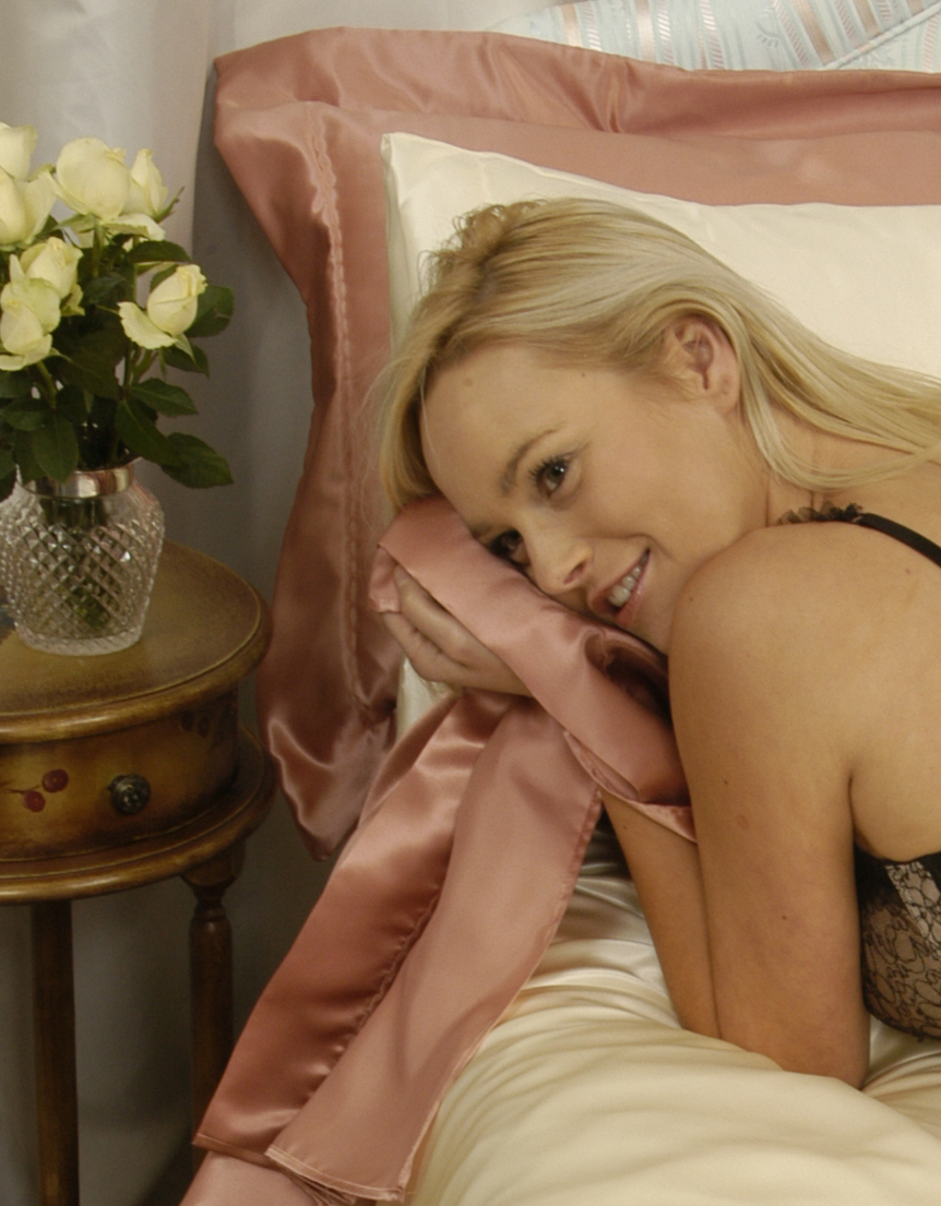 Beautiful blonde girl in silk bed linen