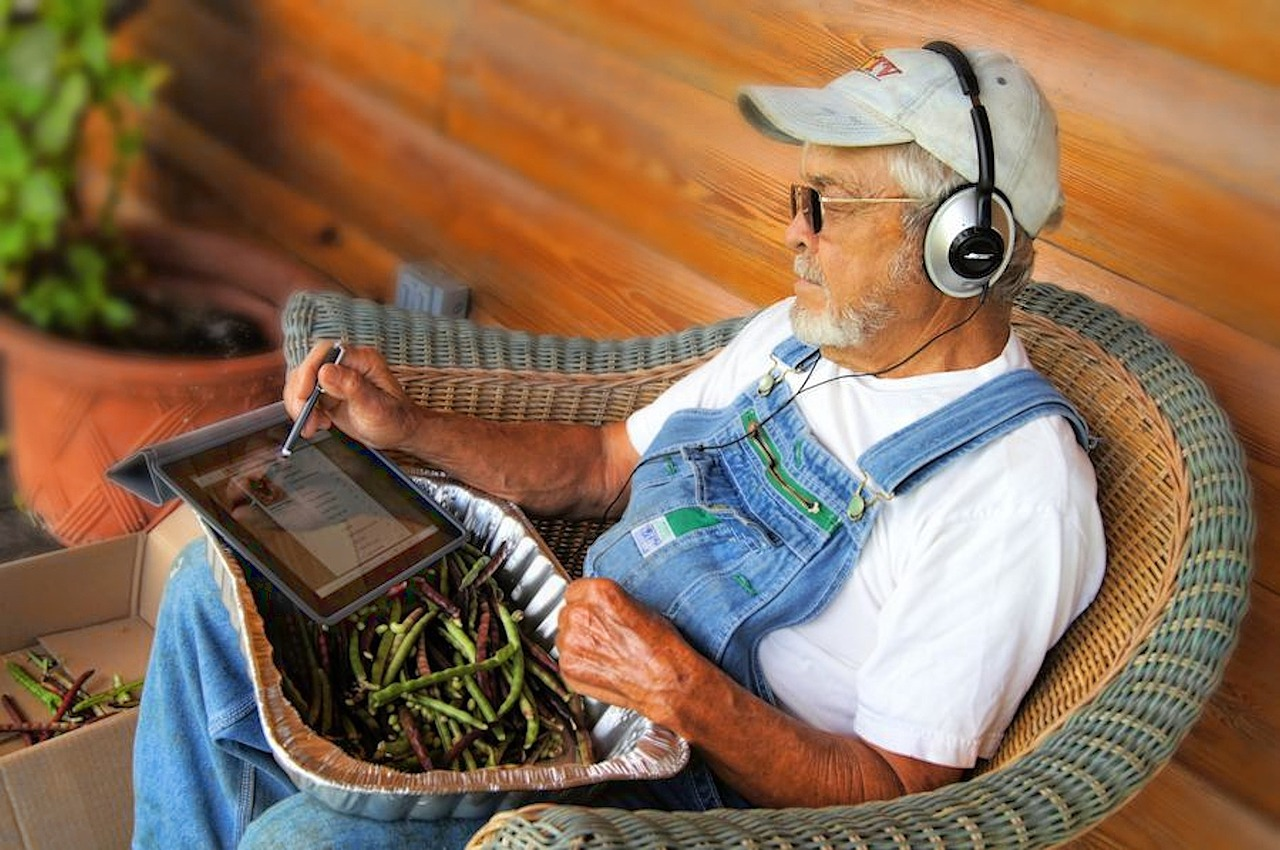 Image of older man with headphones and iPad  showcasing the services offered by Lynden Consulting Ltd, a strategic marketing and communications company founded by Edna Petzen to help health and social care companies improve customer insights, occupancy and business performance