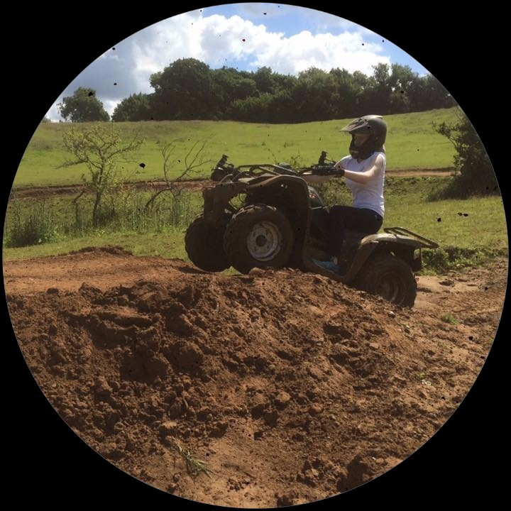 Woman on quad going up a muddy hill.