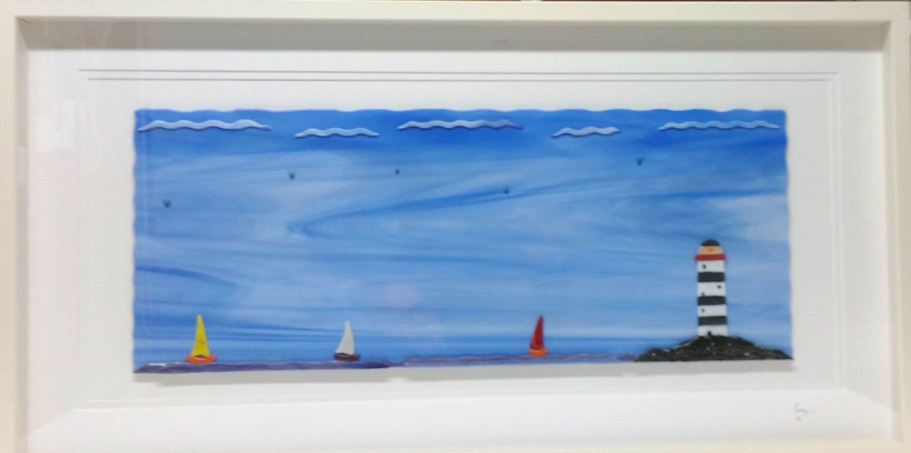 Sky blue Glass Art with black & white  LightHouse perched on rocks.  3 Sailing Boats red,yellow white sails