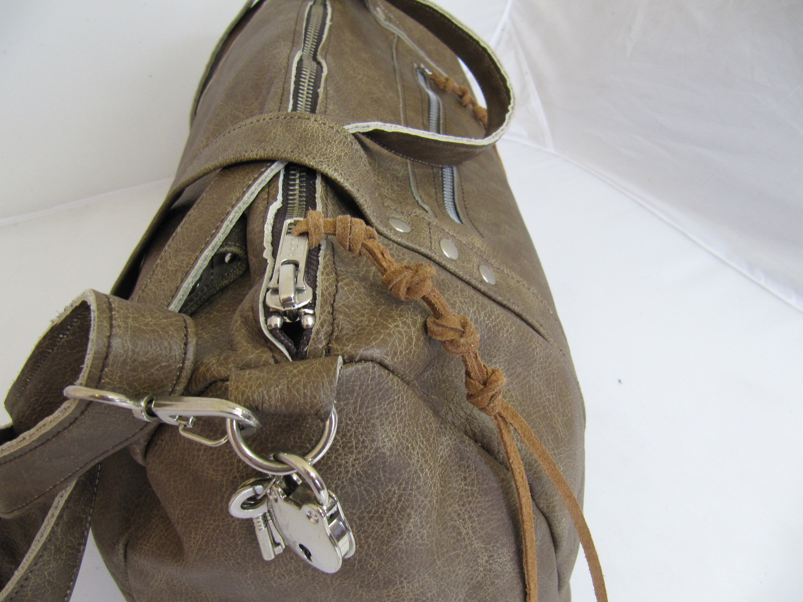 Overnight bag in light vintage leather and silver clips and zips.