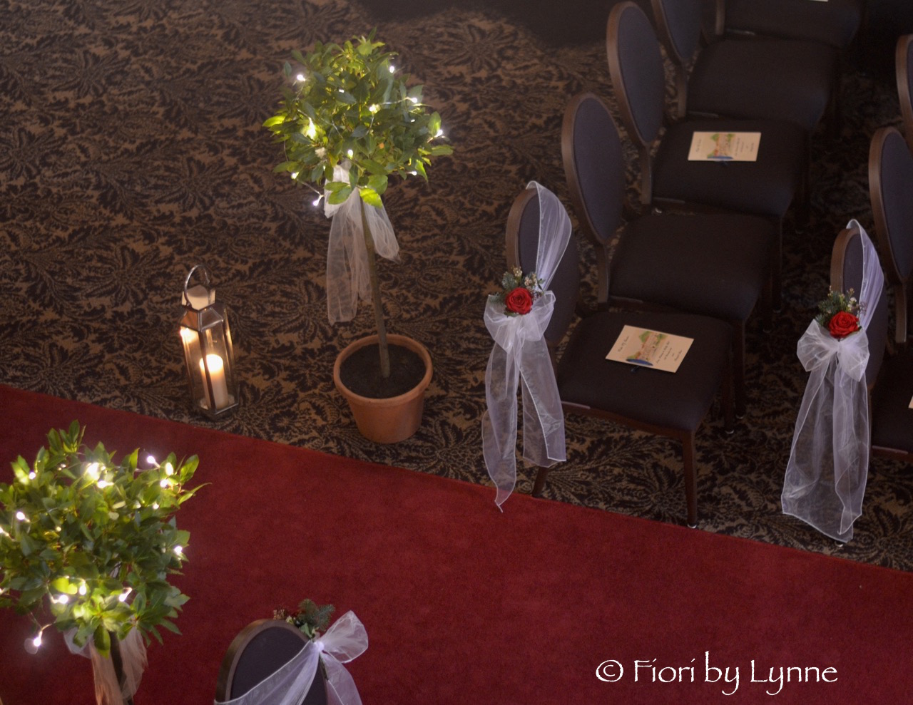 aisle-rhinefieldhouse-winter-chair-flowers-lanterns-baytrees-fairylights.jpg