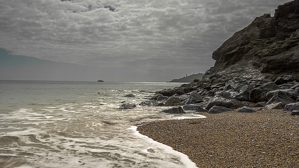 The pebbled beach at Hallsands shimmering with Start Point in the distance. Stock Image ID: 2491