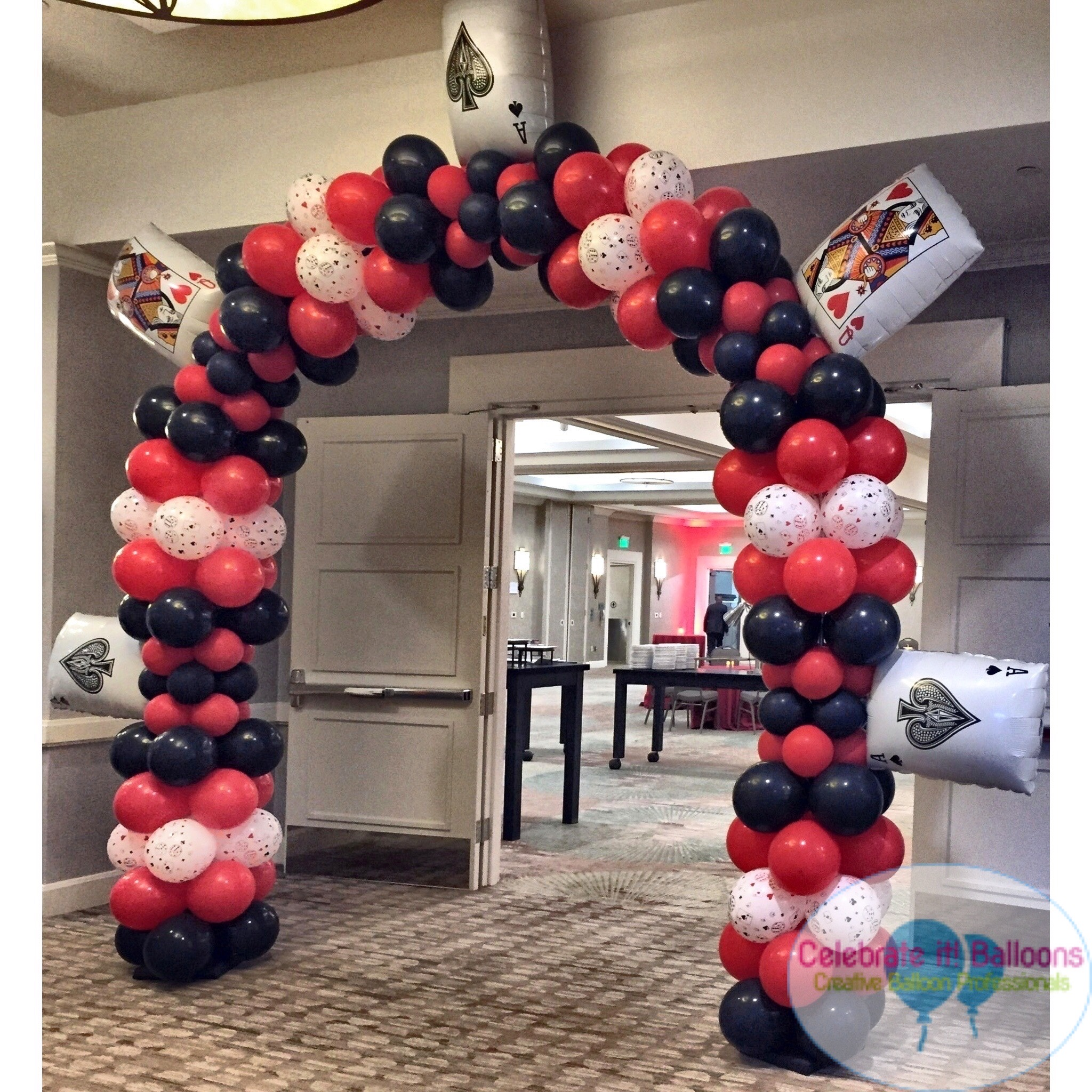 Casino themed balloon arch with playing card balloons in red, black and white