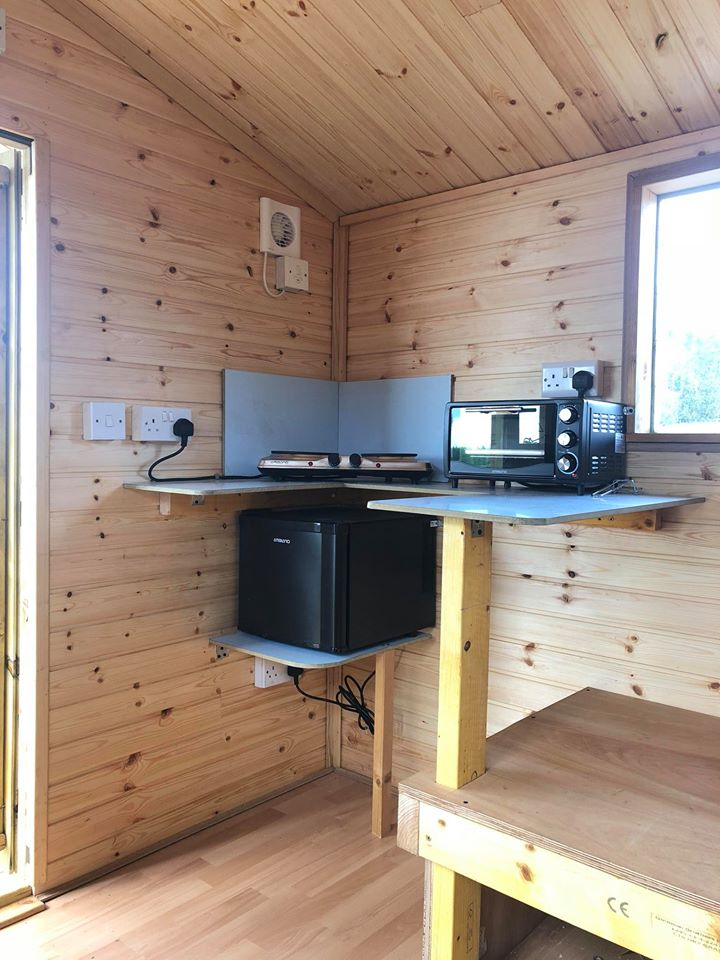The kitchen corner of a glamping shed with fridge, microwave and cooking plates