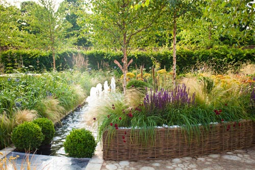sunset over a garden with water feature with mixed planting and box balls for a planting border effect