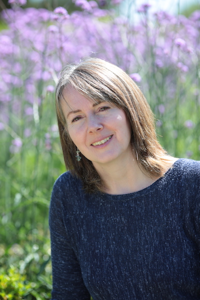 Petrina Banfield author of The Forgotten Girl, seen here in a blue top in front of a field of violet coloured hollyhocks