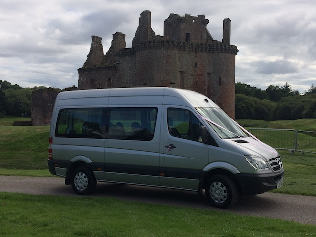 Dowden's minibus at a wedding location decorated with wedding ribbons