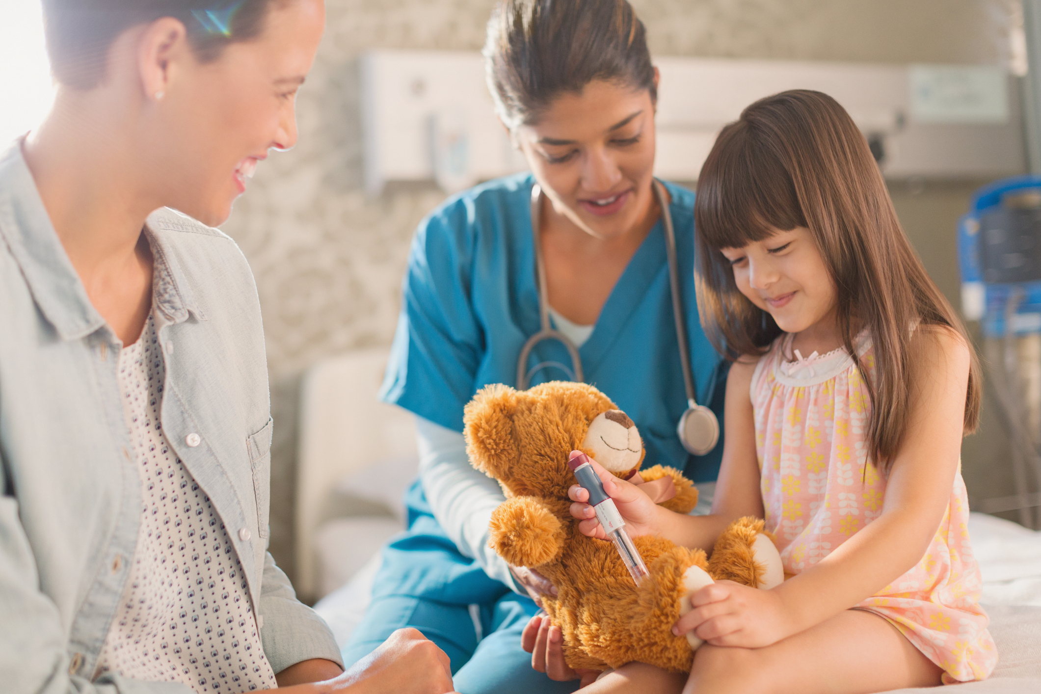 female-nurse-and-mother-watching-girl-patient-using-insulin-pen-on-teddy-bearjpg