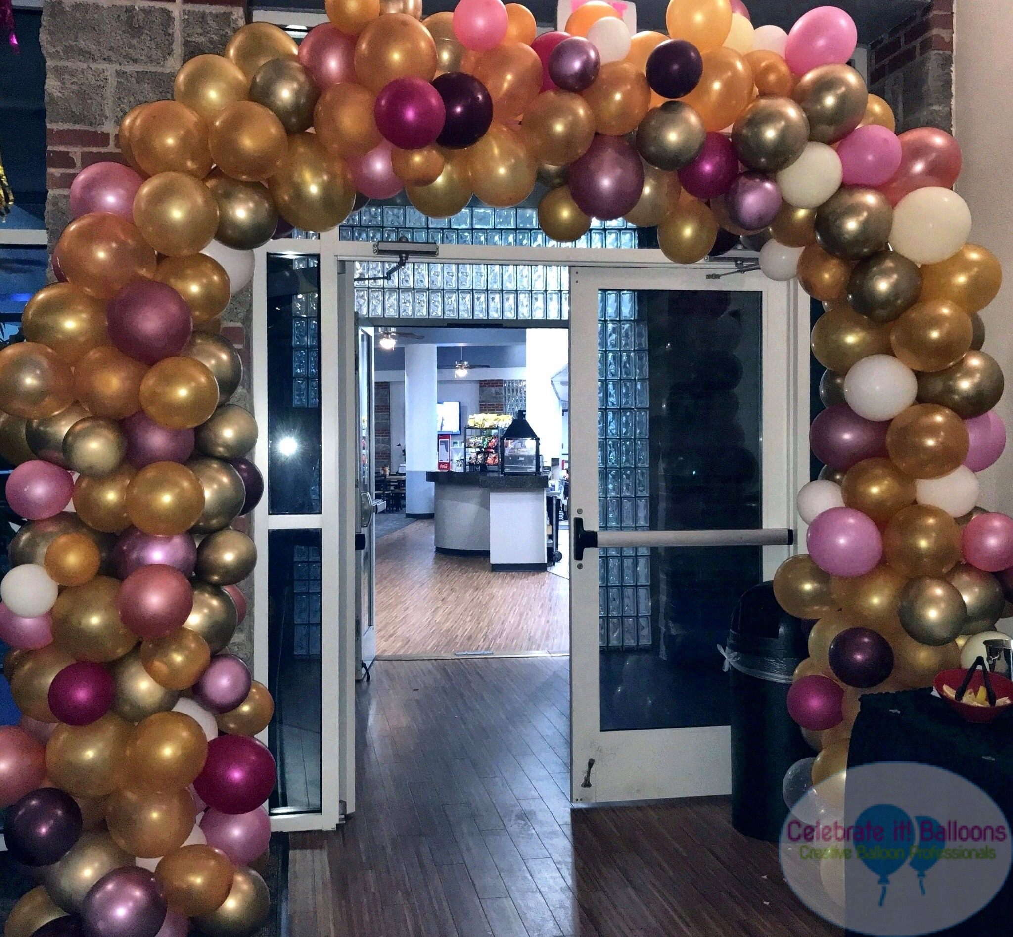 Organic balloon arch shades of pink and gold with white and burgundy