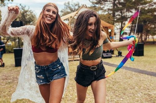 two happy women at a festival laughing, compact towels for festivals