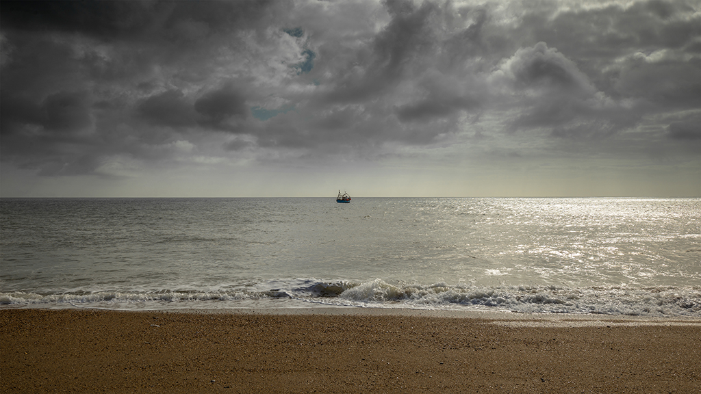 A passing fishing vessel provides a focal point at Hallsands beach. Stock Image ID: 2435