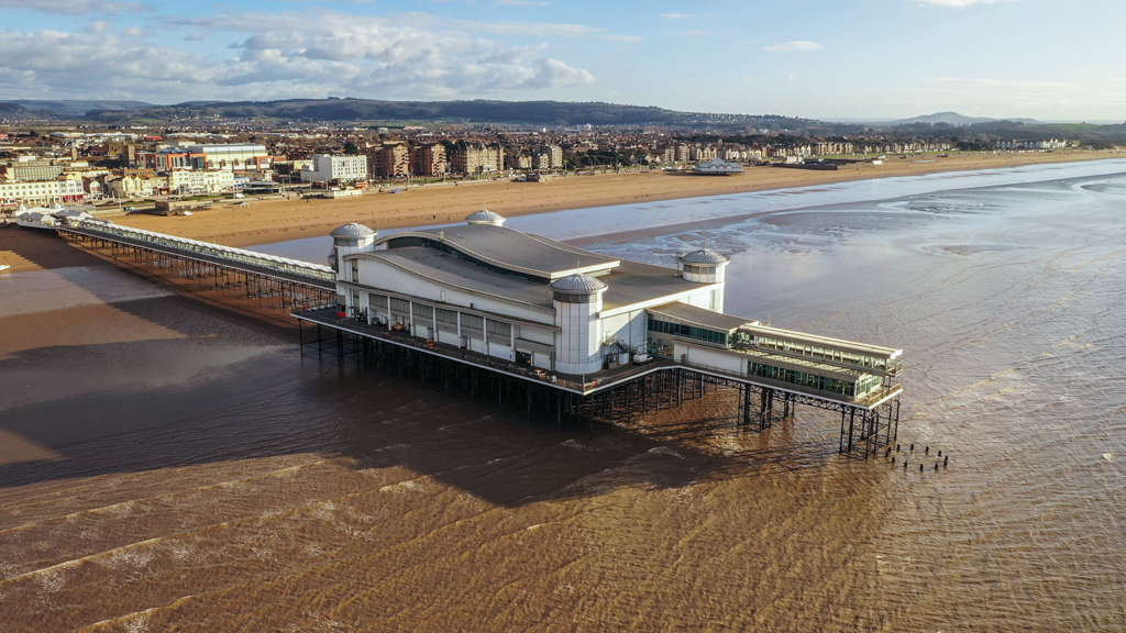 Aerial sequence depicting the Grand Pier at Weston-super-Mare, a popular tourist destination.