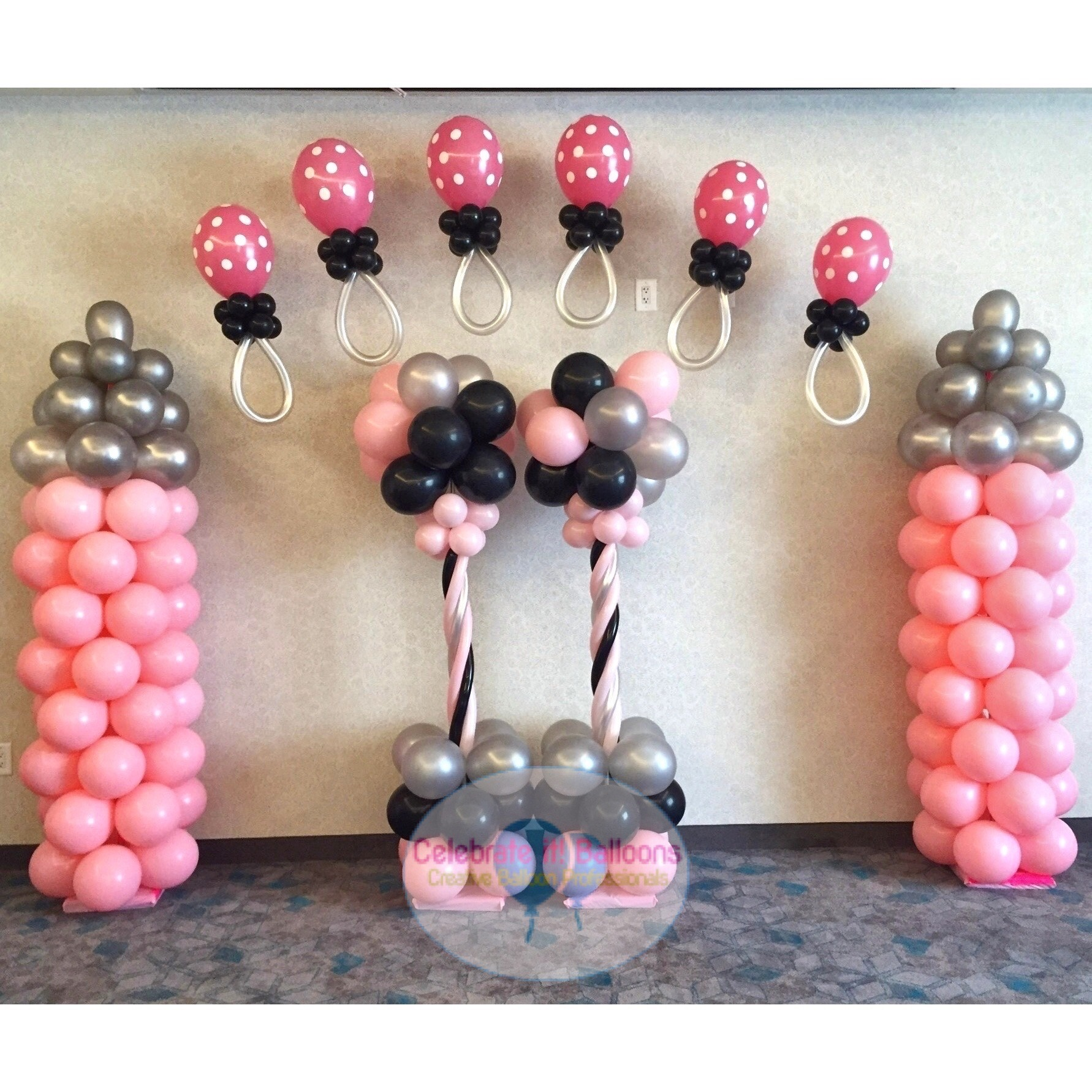 Baby Shower Pacifier Balloon Arch in pink and silver baby bottles with black balloon accents.