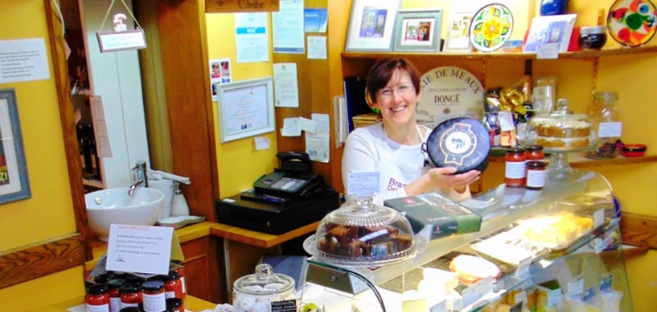 Carrie Merrick in Brambles Deli behind a range of delicious cheeses, chutneys and cakes