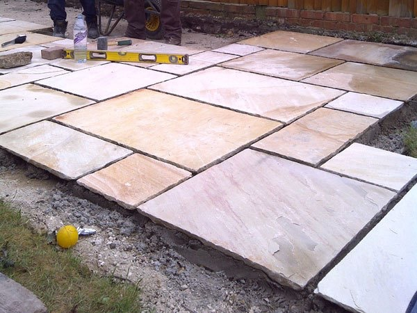 New sandstone patio being constructed in Ashford, Middlesex