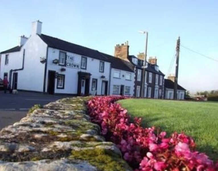 External view of The Crown Hotel Lochmaben, seen from the village green over a sea of pink begonias