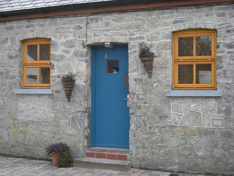 Blue door and pine coloured windows on cottage