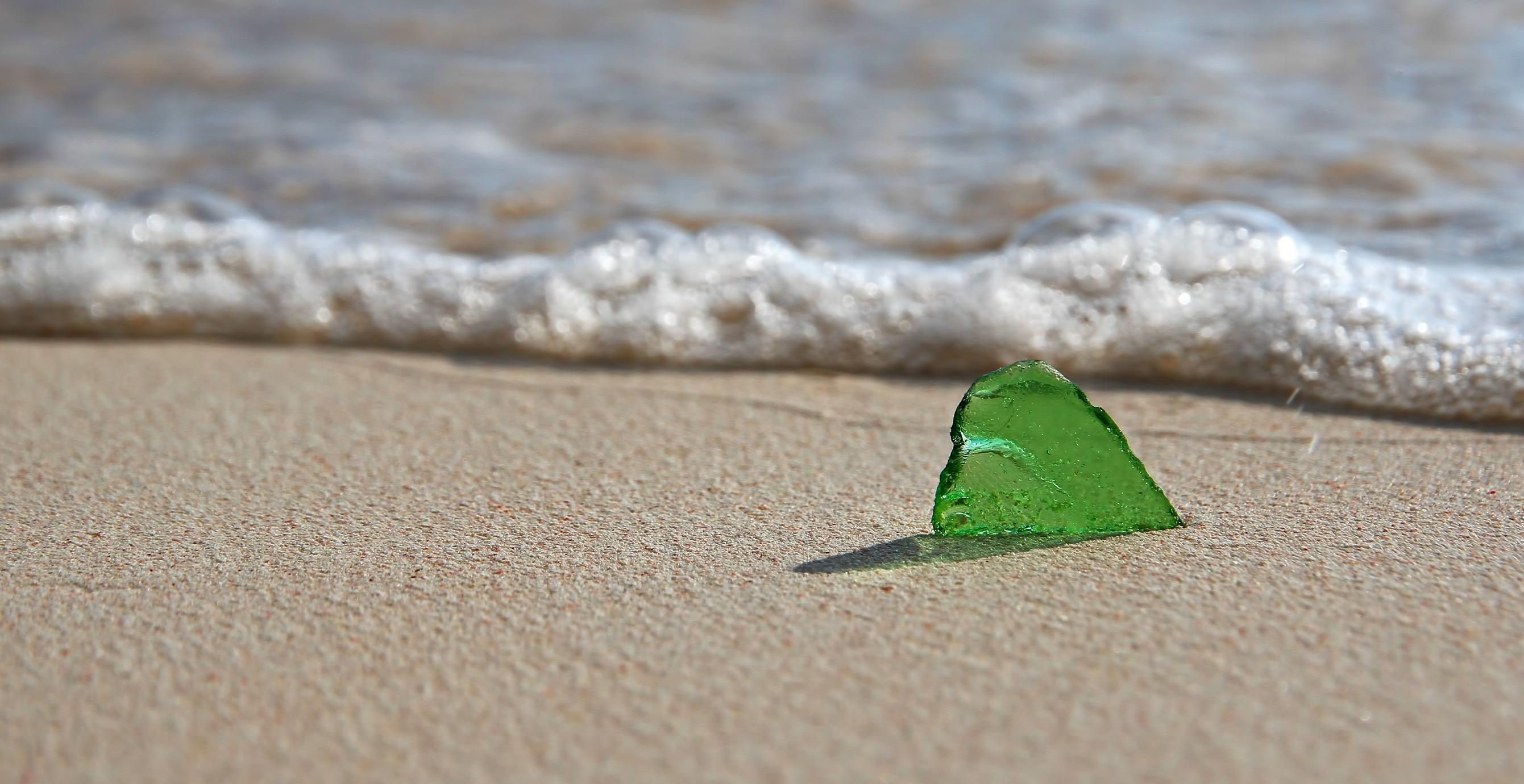 Green sea-glass in sand in front of a wave.