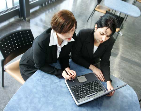 Two ladies leaning over a laptop for a training sessions