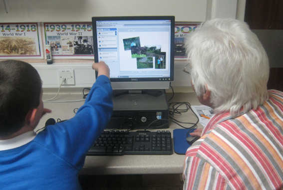 Elderly lady sitting at a computer being taught by a young schoolboy