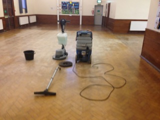 SET UP FOR WOOD FLOOR CLEAN IN A CHURCH HALL