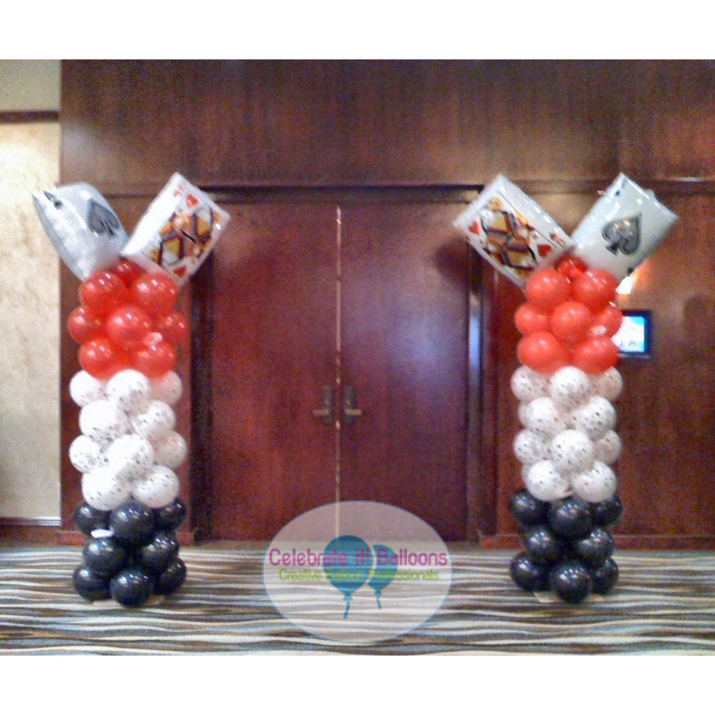 Casino theme balloon columns with jumbo playing card balloons on top