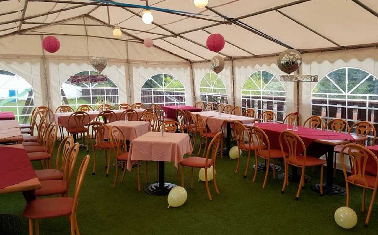A view of the marquee at The Crown Hotel Lochmaben set out with tables of 4, tables of 8 and tables of 6
