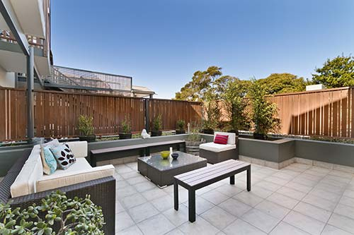 Urban garden with venetian fencing and outdoor sofas