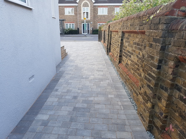 Silver haze block paving used for side path and driveway in Egham, Surrey, viewed from back of path towards front of house